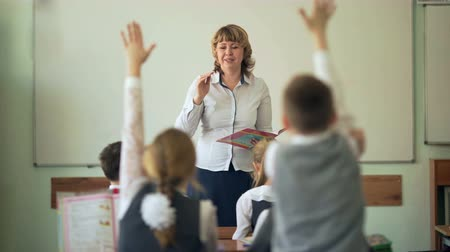 gimnazjum : Pupils raising hands during lesson in classroom at the elementary school