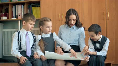 klasa : Elementary school pupil and teacher discussing picture with classmates