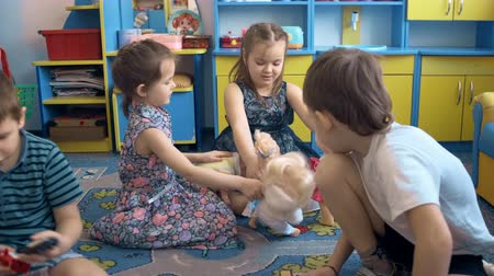 school children : Four children are playing on the floor with toys