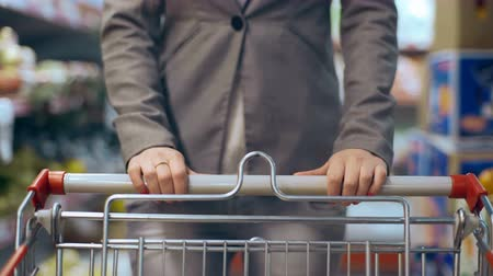 exited : Beautiful young woman with trolley walking in supermarket Stock Footage