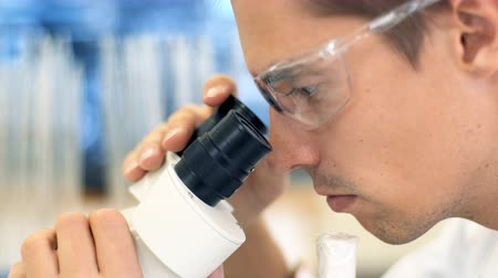 scrutiny : A male scientist working in a lab with microscope