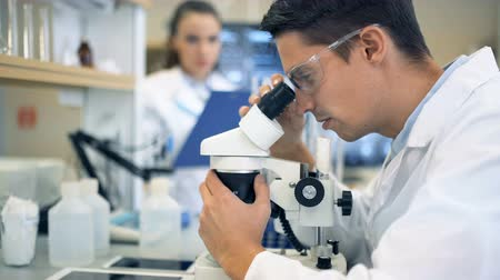 descobrir : A male scientist working in a lab with microscope