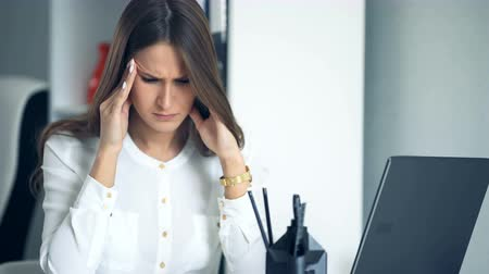 dismissal : Tired business woman at workplace in office, holding her head in hands.