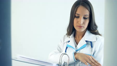 a medicare : Female doctor taking a folder in medical clinic