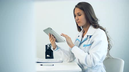 paramedics : Female doctor using tablet computer in medical office Stock Footage