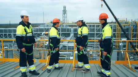 felügyelő : Workers and engineers discussing at refinery , industrial scene in background