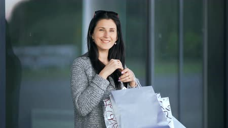 handbag : Happy young fashion woman posing with shopping bags near the mall window Stock Footage