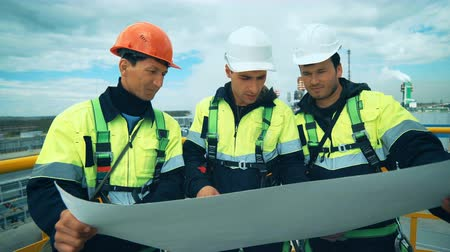 vest : Engineers and workers planning work on industrial plant. Stock Footage