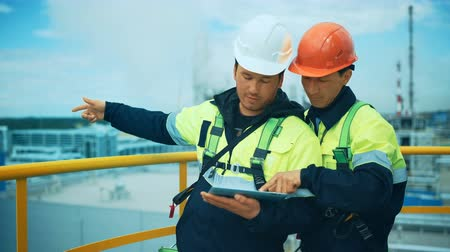 petroleum refinery : Two factory workers discussion with tablet pc. Industrial background