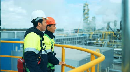 petroleum refinery : Two industrial workers discussion and pointing for inspection