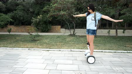 self balancing : Young woman riding electric hover board scooter in green park