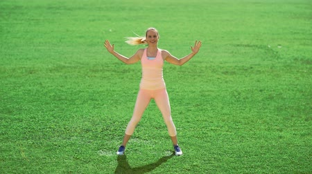 planking : Slim athletic woman doing exercises on green grass Stock Footage