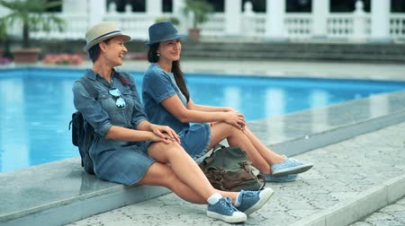 lesbijki : Beautiful young tourist women enjoying talking sitting together near the pool in the park