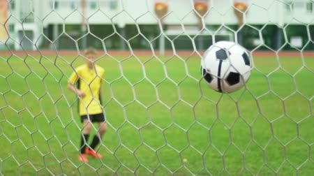 вратарь : A young boy scores a goal during a penalty shoot out. Shot in slow motion