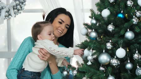 festoon : Mother with her 10 months old baby girl decorating Christmas tree at living room