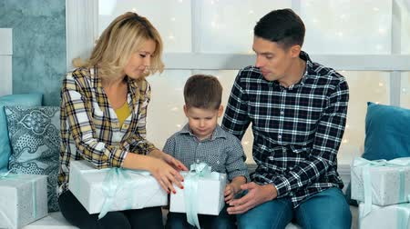 envolto : Smiling parents giving Christmas present to son at home