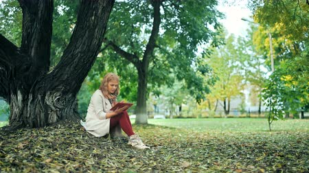yellow jacket : Happy young woman relaxing in autumn park with tablet. Yellow trees, beautiful fall time Stock Footage