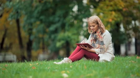 ebook : Young woman using tablet outdoor sitting on grass and smiling.