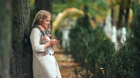 кавказский : Smiling woman in autumn park typing message on the mobile phone