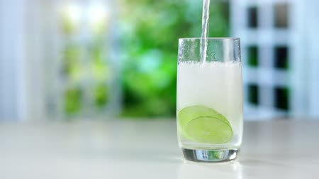 purificado : A refreshing drink being poured into a glass with ice, lemon and lime