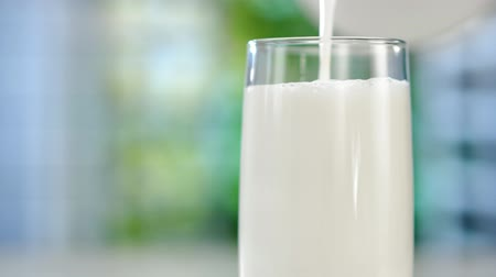 product of : Close-up pouring fresh milk from the jug on table