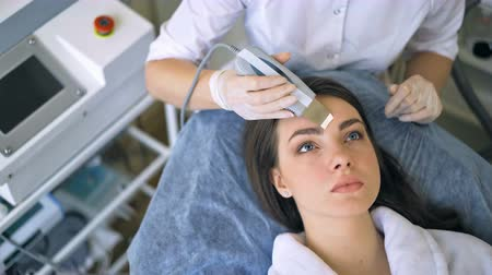 расслаиваться : The cosmetologist makes the procedure ultrasonic face peeling of the facial skin of a beautiful, young woman in a beauty salon Стоковые видеозаписи