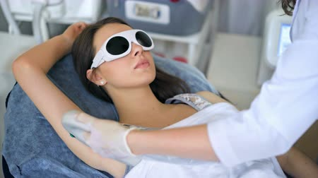 underarm : Beautiful woman getting permanent laser hair removal at beauty salon.