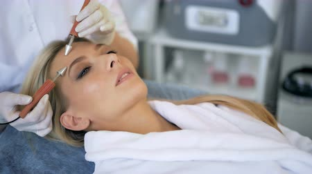 stimulating : Close-up of beautiful woman receiving facial microcurrent treatment from therapist at beaty salon Stock Footage