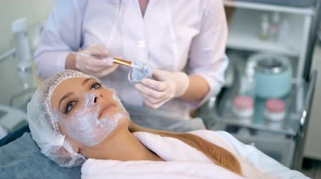 simir : Beautiful woman with facial mask at beauty salon