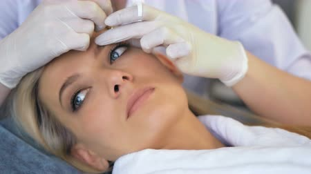 dermatologia : Beautician doing permanent makeup for eyebrows in beauty salon