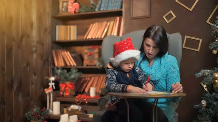 post room : Mother and little son writing letter to Santa Claus