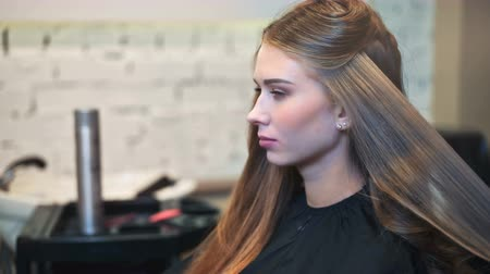 curling hair : Female hairdresser straightening the hair of a client at a salon
