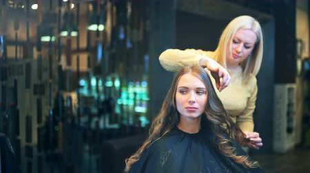 ringlet : Beautiful brunette young woman at the hairdresser salon. Hairdresser making hairstyle Stock Footage