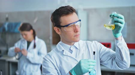 ученый : Young scientist checking test tubes in the lab. Man wears protective goggles