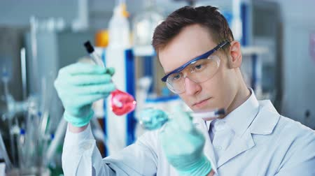 naukowiec : A young man doing an experiment in a chemical laboratory Wideo
