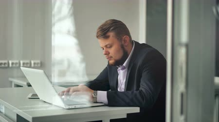портретный : Young businessman working in office, sitting at desk, looking at laptop computer screen Стоковые видеозаписи