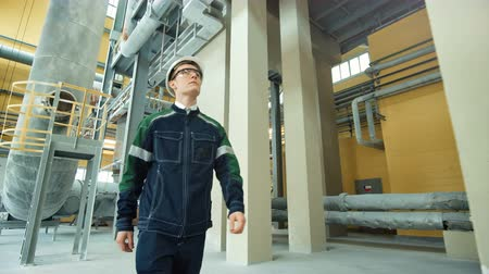 workman : Engineer in hardhat is walking in heavy industry factory Stock Footage
