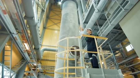 petrokimya : Young engineer wearing protective helmet posing at modern factory