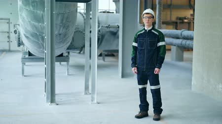 petrokimya : Young engineer wearing protective helmet posing looking at camera at modern factory