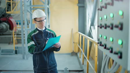 inspector : Engineer signing a document in industrial factory