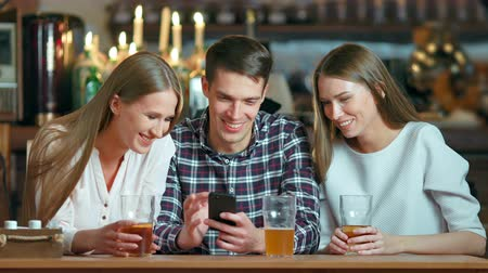 película de filme : Friends using smartphones sitting in the cafe Stock Footage