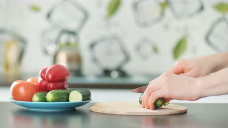 cucumber : Hand with knife cuts vegetables on a wooden cutting board Stock Footage