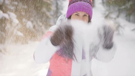 hófúvás : Young woman enjoying sunny winter day, throwing snow outdoors. Slow motion Stock mozgókép