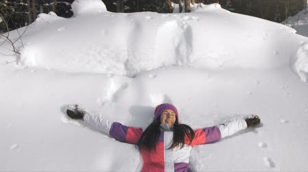 snow angel : Young happy woman making snow angel
