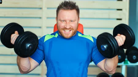 ivászat : Muscular man doing exercises with dumbbells at biceps in gym Stock mozgókép