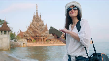 Бангкок : Young woman traveler using digital tablet computer reading guidebook app searching information