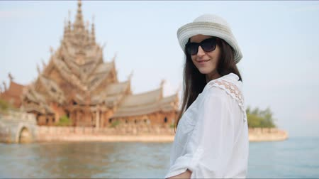 Камбоджа : Young woman touirist smiling and posing in front of the ancient temple. Happy vacation concept