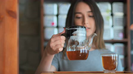 indian tea : Young smiling woman pouring red tea from glass kettle to smal cup Stock Footage