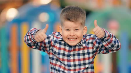 outside : Funny positive little boy gesturing thumbs up on a colourful background