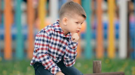 medo : Pensive little boy sitting outside on a colourful background